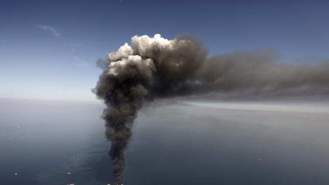 FILE - This Wednesday, April 21, 2010 file photo shows oil in the Gulf of Mexico, more than 50 miles southeast of Venice on Louisiana's tip, as a large plume of smoke rises from fires on BP's Deepwater Horizon offshore oil rig. An April 20, 2010 explosion at the offshore platform killed 11 men, and the subsequent leak released an estimated 172 million gallons of petroleum into the gulf. (AP Photo/Gerald Herbert, File)