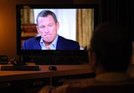 A man in Kensington, Maryland, watches disgraced cycling star Lance Armstrong being interviewed by Oprah Winfrey on January 17, 2013. UCI announced Monday it had disbanded the independent commission it had set up to investigate alleged involvement by the global governing body in the Armstrong doping scandal