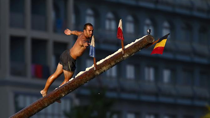 """A competitor reaches out to grab a flag as he slips off the """"gostra"""", a pole covered in grease, during the celebrations for the religious feast of St Julian, patron of the town of St Julian's"""