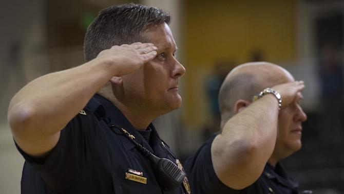 University of Colorado-Colorado Springs police chief Brian McPike, left, and Lt. Clayton Garner salute fallen officer Garrett Swasey during a moment of silence before a college basketball game Saturday, Nov. 28, 2015, in Colorado Springs, Colo. Swasey was killed in a shooting at a Planned Parenthood Clinic in Colorado Springs on Friday. (Christian Murdock/The Gazette via AP) MAGS OUT; MANDATORY CREDIT