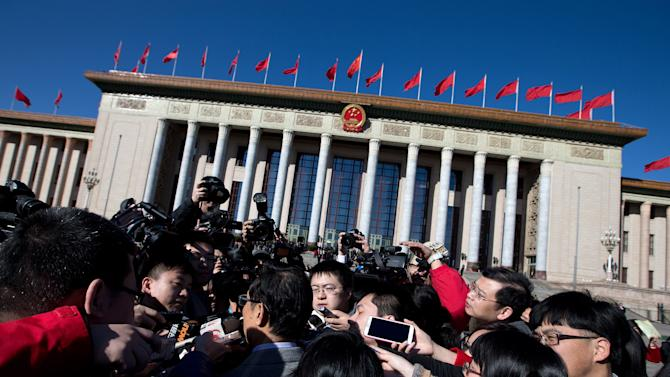 A delegate is mobbed by journalists as he arrives for sessions of the National People's Congress and the Chinese People's Political Consultative Conference at the Great Hall of the People, in Beijing Monday, March 4, 2013. The National People's Congress, which opens Tuesday, completes the leadership power transition initiated four months ago, approving top government appointments and giving the new leaders a platform to lay out policies. (AP Photo/Andy Wong)