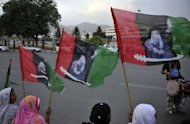 Activists of the ruling Pakistan People&#39;s Party (PPP) carry party flags with the pictures of slain former Pakistani premier Benazir Bhutto outside the lower house of parliament in Islamabad. MPs elected Raja Pervez Ashraf as Pakistan&#39;s new prime minister Friday, in a bid to end a crisis sparked by judges ousting the premier and demanding the arrest of his would-be successor