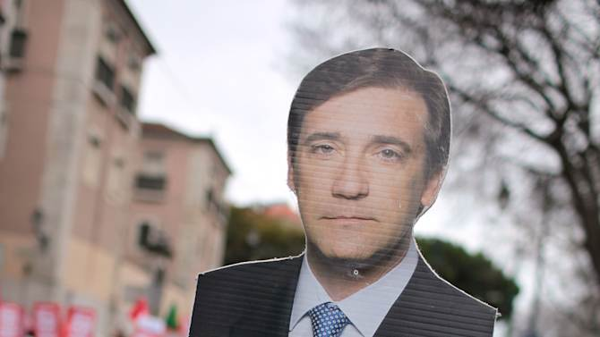 """A demonstrator carries a photo of Portuguese Prime Minister Pedro Passos Coelho with the label """"thief"""" during an anti-austerity protest march in Lisbon Saturday, Feb. 16 2013. The protest was called by CGTP, the Portuguese confederation of workers unions. (AP Photo/Armando Franca)"""