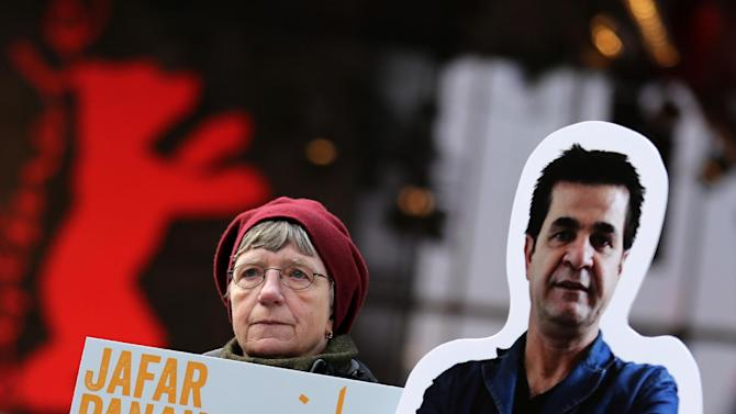 "A protester shows a banner next to a portrait of Iranian director Jafar Panahi prior to the screening of the movie 'Closed Curtain' during the 63rd annual Berlin International Film Festival in Berlin, Germany, Tuesday Feb.12. 2013. The  movie from the  dissident Iranian director that defies a ban on filmmaking and reflects his frustration at being unable to work officially is making its debut at the Berlin film festival. ""Closed Curtain"" is co-directed by Jafar Panahi and fellow Iranian filmmaker and his longtime friend Kamboziya Partovi. Panahi, who has won awards at several major film festivals in the past, was sentenced to house arrest and a 20-year ban on filmmaking in 2011 after being convicted of ""making propaganda"" against Iran's ruling system.  Partovi presented the movie Tuesday at the Berlin festival, where it's one of 19 films competing for the top Golden Bear award. It's filmed entirely inside a seaside villa, much of the time with curtains drawn, and the two directors are the lead actors. (AP Photo/dpa, Kay Nietfeld)"