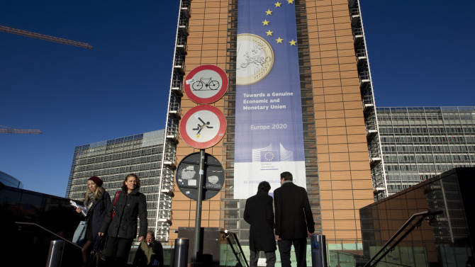 People walk in front of a giant banner for the euro currency outside of an EU summit in Brussels on Thursday, Nov. 22, 2012. Leaders from around Europe are arriving in Brussels Thursday for what promises to be a turbulent summit on the budget for the 27-country European Union. And for once, Britain will be at the heart of the debate. (AP Photo/Virginia Mayo)