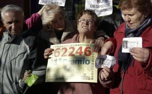 "Pensioners, who won part of the first prize of ""El Gordo"", celebrate outside a lottery shop where the lottery number was sold in Leganes"