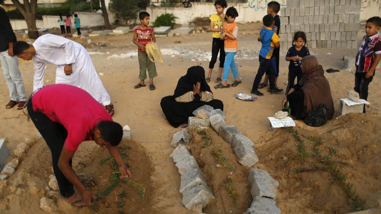 Palestinians mourn at the graves of their relatives, who medics said were killed during the Israeli offensive, at a cemetery in Beit Lahiyah in the northern Gaza Strip