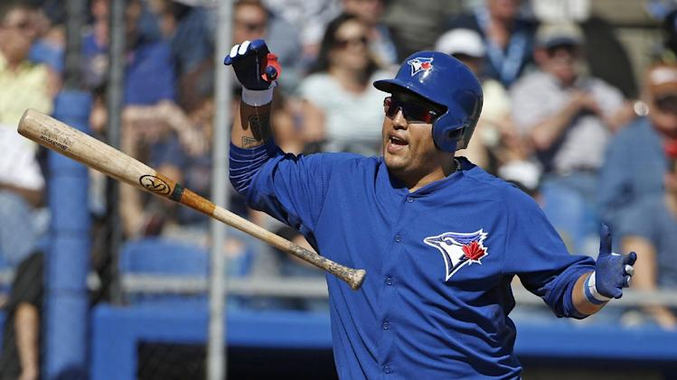 Toronto Blue Jays' Dioner Navarro tosses his bat after striking out swinging with Melky Cabrera on first in the sixth inning of a spring training baseball game against the Minnesota Twins in Dunedin, Fla., Saturday, March 8, 2014