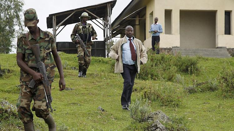 FILE  - In this Dec. 5, 2012 file photo, Jean-Marie Runiga, center, then president of Congo's M23 rebel group, walks with his security guards near the Congo-Uganda border town of Bunagana. A spokesman said Thursday, Feb. 28, 2013, that Runiga has been dismissed by the group's military leader over accusations that he is supporting Bosco Ntaganda, a wanted war criminal. The move has split the M23 as a new group has been formed by those who still support Runiga, including Gen. Baudoin Ngaruye, the second-ranked military leader of the group. (AP Photo/Jerome Delay, File)