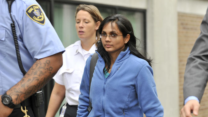 Annie Dookhan, center, leaves a Boston courthouse escorted by court officers and her lawyer after refusing to testify in a drug case against Shawn Drumgold, Wednesday, Oct. 10, 2012. Dookhan is accused of faking drug results, forging signatures and mixing samples a state police lab. State police say Dookhan tested more than 60,000 drug samples involving 34,000 defendants during her nine years at the lab.. (AP Photo/Josh Reynolds)