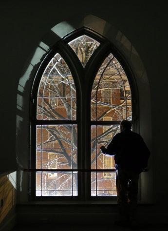 In this Jan. 15, 2013 photo, Jeff Jerome looks out of a window in Westminster Hall, which overlooks the cemetery that is home to Edgar Allan Poe&#39;s grave, in Baltimore. For years, Jerome watched as a mysterious man known as the Poe Toaster left three roses and an unfinished bottle of cognac at Poes grave every year on the legendary writers birthday. His identity is a great modern mystery, and just as mysteriously, the tradition ended four years ago. (AP Photo/Patrick Semansky)