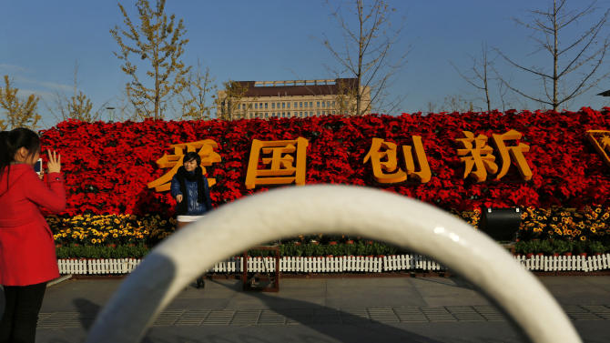 "In this photo taken Monday, Nov. 12, 2012, a woman poses for photos near floral decorations with the Chinese characters for ""Patriotism, Innovation"" set up for the 18th Communist Party Congress held in Beijing, China. The Chinese capital's administrators have bedecked the city with towers of flower installations and other eye-catching landscaping decorations. State media say 20 million pots of flowers are being used in more than a hundred locations in preparation for the once-a-decade party congress to usher in a new generation of leaders.  (AP Photo/Vincent Yu)"