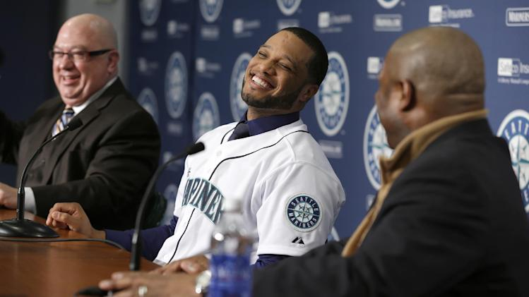 Robinson Cano, center, laughs as he is introduced as the newest member of the Seattle Mariners baseball team on Thursday, Dec. 12, 2013, in Seattle. Mariners general manager Jack Zduriencik, left, and manager Lloyd McClendon, right, look on. (AP Photo/Ted S. Warren)