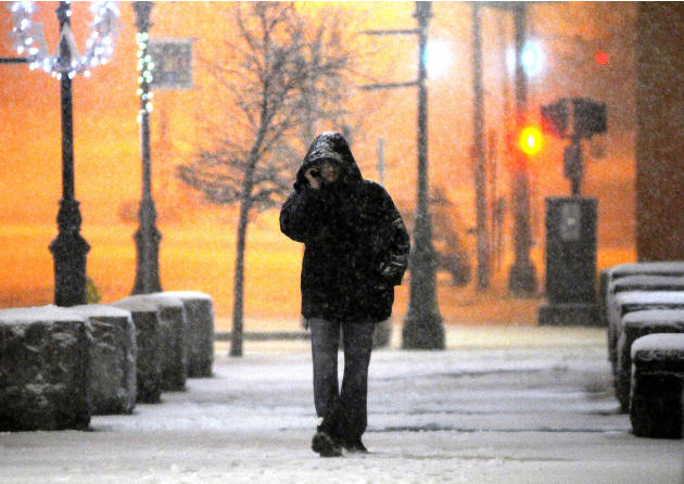 In this Wednesday, Dec. 26, 2012 photo, a man talks on his cellphone, as he walks along Main Street during a snowstorm late Wednesday night.  The winter storm brought snow to inland parts of the North