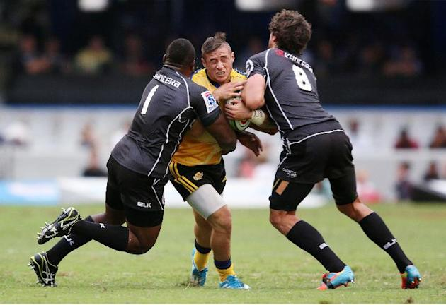 TJ Perenara (C) of the Wellington Hurricanes vies with Tendai Mtawarira (L) and Ryan Kankowski of the Cell C Sharks during the Super 15 rugby union held at the Growthpoint Kings Park Rugby Stadium in