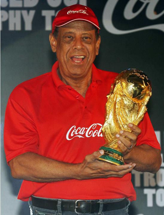 Former Brazilian national soccer team captain Carlos Alberto Torres holds the World Cup trophy during the FIFA World Cup Trophy Tour, in Kolkata
