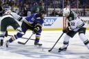 Minnesota Wild's Matt Dumba, left, collides with St. Louis Blues' Patrik Berglund (21), of Sweden, as Berglund and Wild's Nino Niederreiter, of Switzerland, chase after a loose puck during the second period in Game 2 of an NHL hockey first-round playoff series, Saturday, April 18, 2015, in St. Louis. (AP Photo/Jeff Roberson)