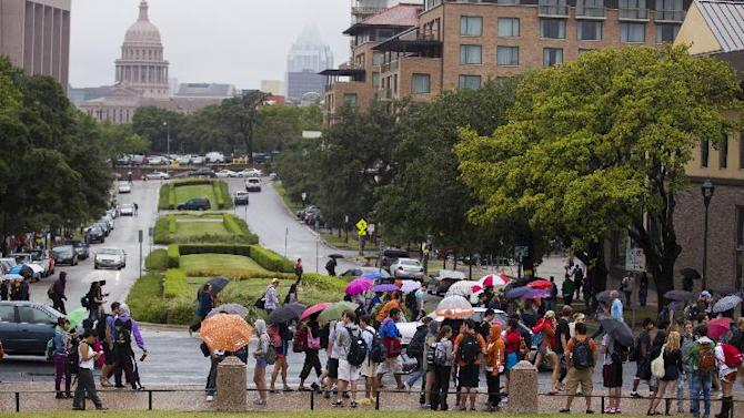 University of Texas students stand outside after evacuating buildings at The University of Texas on Friday, Sept. 14, 2012 in Austin, Texas. Thousands of people streamed off university campuses in Texas and North Dakota on Friday after phoned-in bomb threats prompted evacuations and officials warned students and faculty to get away as quickly as possible. No bombs were found on either campus by early afternoon and it was not clear whether the threats were related. (AP Photo/Statesman.com, Ricardo B.Brazziell)  MAGS OUT; NO SALES; INTERNET AND TV MUST CREDIT PHOTOGRAPHER AND STATESMAN.COM