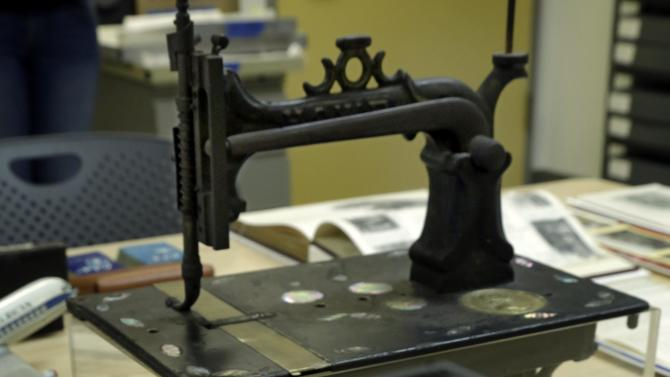 """A Howe sewing machine catalog cover and sewing machine, by Elias Howe, who is buried in New York's Green-Wood Cemetery, is displayed at the Museum of the City of New York, prior to its installation in the """"A Beautiful Way To Go: New York's Green-Wood Cemetery,""""  exhibit, Thursday, May 9, 2013. (AP Photo/Richard Drew)"""