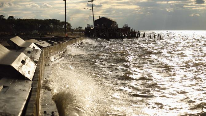 Waves pound the seawall near a crab house on Saxis Island in Virginia