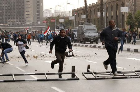 Anti-government protesters run as police arrive during their attempt to walk into Tahrir square in Cairo