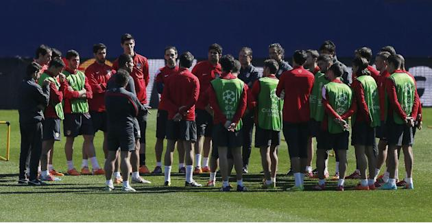 Atletico Madrid coach Diego Simeone, of Argentina,talks to players, seventh from the left, centre, during a training session ahead of Tuesday's Champions League, round of 16, second leg, soccer ma