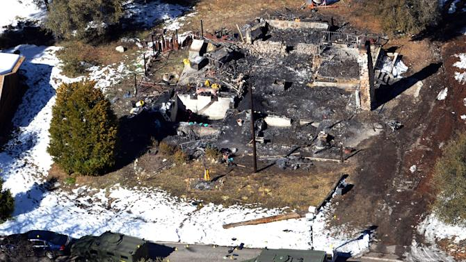 FILE - This Feb. 13,2013 file photo this aerial photo, law enforcement authorities investigate the burnt-out cabin where accused quadruple-murder suspect Christopher Dorner was believed to have died after barricading himself inside, during a stand-off with police in the Angeles Oaks area of Big Bear, Calif.   A Southern California city's decision not to make good on a promise to pay a $100,000 reward in the case of the rogue ex-Los Angeles officer is the latest wrinkle in the battle over the pot of money that remains unpaid more than six weeks since the fugitive's death.  (AP Photo/The Sun, John Valenzuela,File)