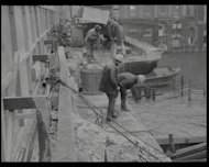 This newsreel shows London Bridge being taken apart after 140 years of service. It was sold off and replaced by a bigger one that was opened by The Queen five years later.