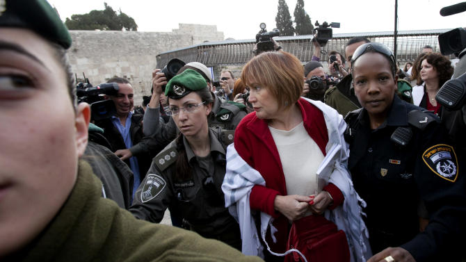 An Israeli woman is arrested for wearing a prayer shawl at the Western Wall in Jerusalem, Thursday, April 11, 2013. Israeli police have detained five women while praying at the Western Wall in Jerusalem for performing religious rituals that ultra-Orthodox Jews say are reserved for men. Police spokesman said about 120 woman arrived for their monthly prayer service Thursday and five were detained for wearing prayer shawls. (AP Photo/Michal Fattal)