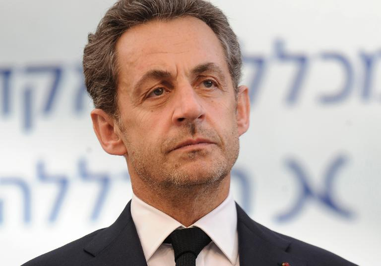 Former French president Nicolas Sarkozy listens on during a ceremony