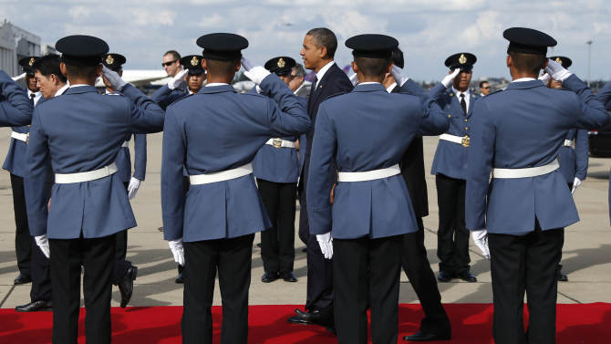 U.S. President Barack Obama, center, walks down a red carpet through saluting military guards of honor as he arrives on Air Force One at Don Mueang International Airport in Bangkok, Thailand, Sunday, Nov. 18, 2012. (AP Photo/Carolyn Kaster)
