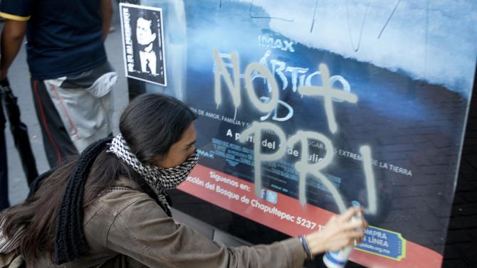 "A protester spray paints the words in Spanish ""No more PRI,"" referring to the former ruling Institutional Revolutionary Party, during a protest against Mexico's President-elect Enrique Pena Nieto, of the PRI, in Mexico City, Friday, Aug. 31, 2012. On Friday, the Federal Electoral Tribunal declared Pena Nieto won the majority of votes in last July's presidential election, and he will be sworn-in on Dec. 1. (AP Photo/Eduardo Verdugo)"