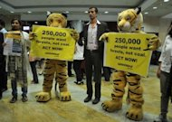 Greenpeace activists wearing tiger costumes hold placards outside the venue before the opening session of Conference of the Parties (COP 11) during the Convention on Biodiversity in Hyderabad
