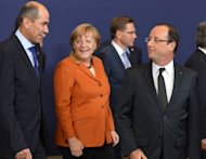 French President Francois Hollande (R) speaks with Slovenian Prime Minister Janez Jansa (L) and German Chancellor Angela Merkel (C) after group photo at the EU summit in Brussels. EU leaders Thursday vowed to set up a banking union during the course of 2013 after a Franco-German spat held up agreement on exactly when this vital crisis-fighting tool might come into force