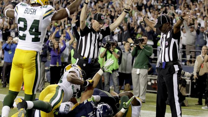 Sept. 24 FILE - In this Sept. 24, 2012, file photo, an official, rear center, signals for a touchdown by Seattle Seahawks wide receiver Golden Tate, obscured, as another official, at right, signals a touchback on the controversial last play of an NFL football game against the Green Bay Packers in Seattle. The Seahawks won 14-12. The NFL and the referees' union have reached a tentative contract agreement on Wednesday, Sept. 26, ending an impasse that began in June when the league locked out the officials and used replacements instead. (AP Photo/Stephen Brashear, File)