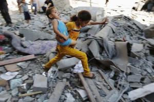 A Palestinian girl carries a child across rubble from …