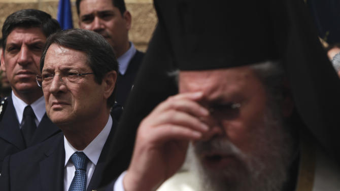 Cyprus' President Nicos Anastasiades, left, and Orthodox Christian church Archbishop Chrysostomos II are seen during a wreath-laying ceremony at a memorial during the country's guerrilla campaign against Britain's colonial rule between 1955-1959 in Central Prisons for fighters killed in capital Nicosia on Monday April 1, 2013. April 1, is a national holiday in Cyprus marking the start of the campaign that aimed for union with Greece, but resulted in the island's independence in 1960. Cyprus is in the midst of its worst financial crisis in decades with its banking sector in tatters following an agreement with international lenders for a 16 billion euro rescue package. Anastasiades said that his government is hard at work putting together a package of measures aimed at restarting the deeply slumping economy. (AP Photo/Petros Karadjias)