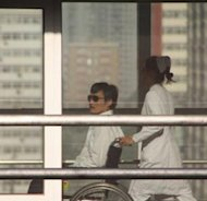 Chinese activist activist Chen Guangcheng (L) is seen in a wheelchair pushed by a nurse at the Chaoyang hospital in Beijing on May 2, 2012. His escape from the heavily guarded home last month became a major diplomatic affair after he sought refuge in the US embassy in Beijing days ahead of a visit by US Secretary of State Hillary Clinton