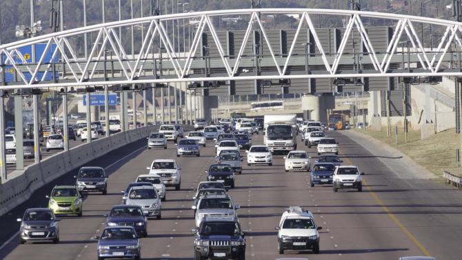 Cars stream underneath a gantry Friday, May 4, 2012, which is planned to use sophisticated electronic equipment to impose toll charges onto the vehicle owners as they pass along the road into Pretoria, South Africa.  South African unions and big business joined to oppose tolls to pay for road upgrades for the nation's commercial hub, saying an irrational plan was being imposed on citizens by the African National Congress (ANC).  Four days before the the system was scheduled to start, the ANC announced the project would be postponed to allow time to talk to unions and business leaders about the toll system. (AP Photo/Denis Farrell)