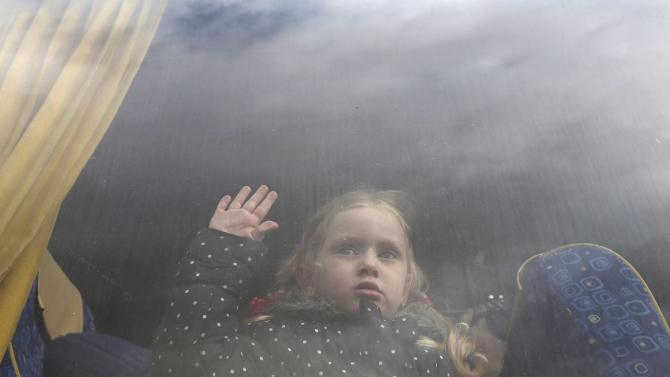 Girl, hoping to cross into Egypt with her family, looks out a bus window at the Rafah crossing between Egypt and the southern Gaza Strip