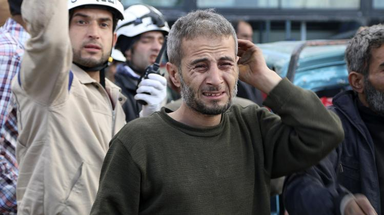A man reacts at site hit by what activists said were barrel bombs dropped by forces loyal to President al-Assad in Aleppo