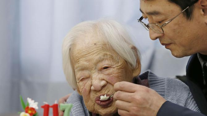 Japanese Okawa, the world's oldest living person, is helped to eat her birthday cake as she celebrates her 117th birthday at an elder care facility in Osaka