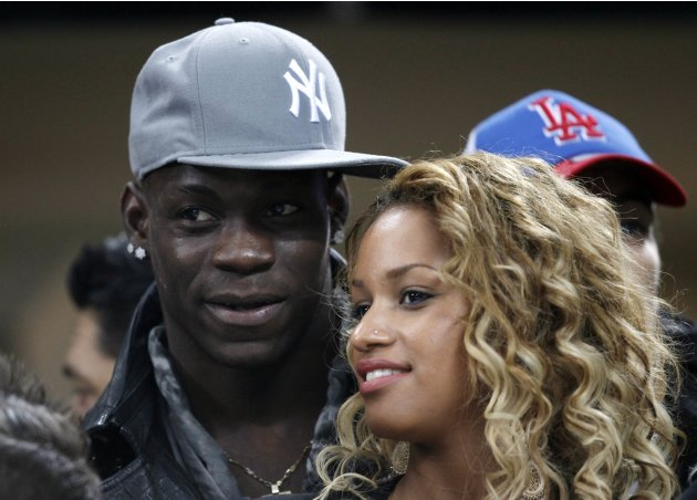 AC Milan's Balotelli stands next to his girlfriend, model Fanny Robert Neguesha, as they watch their Champions League soccer match against Barcelona at the San Siro stadium in Milan