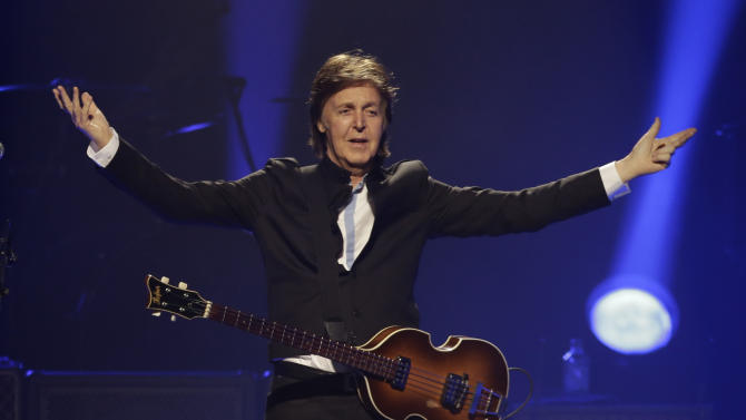 """FILE - In this Saturday, May 18, 2013 file photo, Paul McCartney performs during the first U.S concert of his """"Out There"""" tour, in Orlando, Fla. McCartney made his first visit to the one-time home of the King of Rock 'N' Roll and left a gift behind. According to the official Twitter account of the former Beatle, McCartney dropped a personal guitar pick on Elvis Presley's grave, Sunday, May 26, 2013, and said it was """"so Elvis can play in heaven."""" (AP Photo/John Raoux, File)"""