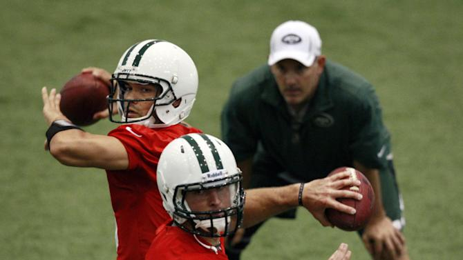 FILE - In a Tuesday, June 12, 2012, file photo, New York Jets quarterbacks coach Matt Cavanaugh, right, watches as Mark Sanchez, left, and Tim Tebow throw during NFL football practice in Florham Park, N.J. Likely done in New York after one frustrating season and Jacksonville already saying no to a happy homecoming, what's next for Tebow, one of the league's most popular and polarizing players? A backup role on another NFL team? A position change? The Canadian Football League? Well, even Tebow isn't sure. (AP Photo/Mel Evans, File)