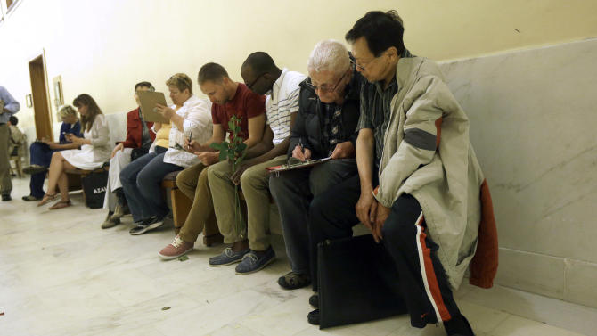 "Gordon Yim, from right, watches as Martin D. Vatis fills out a marriage license application as they wait in line next to Byron Lindsay and Rich Dillon at City Hall in San Francisco, Friday, June 28, 2013. A three-judge panel of the 9th U.S. Circuit Court of Appeals issued a brief order Friday afternoon dissolving, ""effective immediately,"" a stay it imposed on gay marriages while the lawsuit challenging the ban advanced through the courts. (AP Photo/Jeff Chiu)"