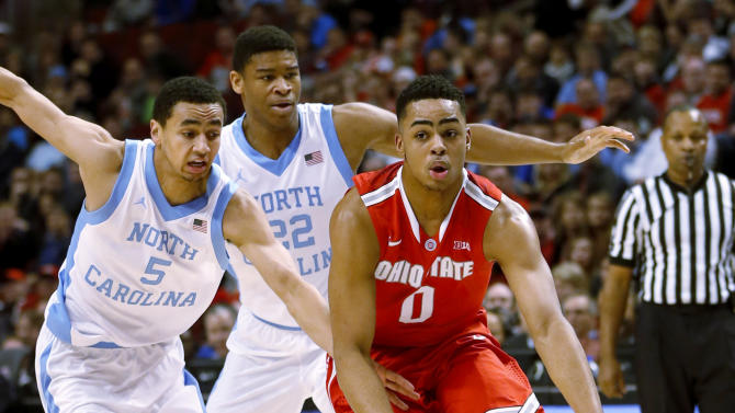 Ohio State guard D'Angelo Russell (0) controls the ball as he looks to a pass against North Carolina guard Marcus Paige (5) and forward Isaiah Hicks (22)during the first half of an NCAA college basketball game on Saturday, Dec. 20, 2014, in Chicago. (AP Photo/Charles Rex Arbogast)
