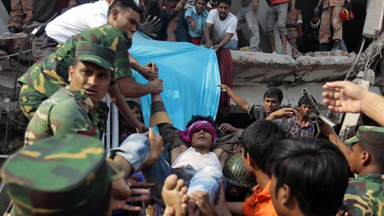 Rescuers carry a survivor out from the debris of a building that collapsed in Savar, near Dhaka, Bangladesh, Wednesday, April 24, 2013. An eight-story building housing several garment factories collapsed near Bangladesh's capital on Wednesday, killing dozens of people and trapping many more under a jumbled mess of concrete. Rescuers tried to cut through the debris with earthmovers, drilling machines and their bare hands. (AP Photo/A.M.Ahad)