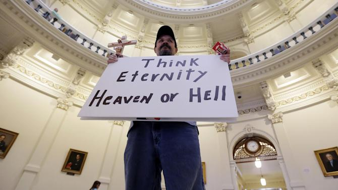 Anti-abortion supporter Juan Gaona, of San Antonio, holds a sign as he prays in the rotunda of the Texas Capitol, Monday, July 8, 2013, in Austin, Texas. The fight over access to abortion in Texas resumed Monday with thousands expected to attend a marathon Senate hearing and a nighttime anti-abortion rally at the Capitol. (AP Photo/Eric Gay)