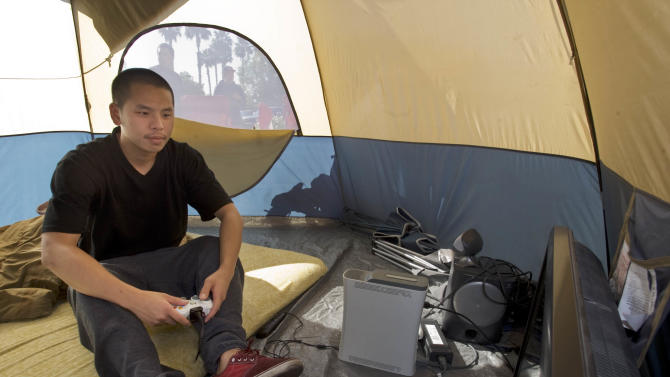 Danny Tran, of Westminster, Calif., plays XBox in his tent outside Best Buy, Tuesday, Nov. 22, 2011, in Westminster, Calif. He's been camping in front of the store since Sunday awaiting to get Black Friday deals on a TV and laptop. (AP Photo/The Orange County Register, Joshua Sudock) ///ADDITIONAL INFO: bestbuylines.1122  - 11/22/11  - PHOTO BY JOSHUA SUDOCK, THE ORANGE COUNTY REGISTER - People camping out in front of Best Buy at the Westminster Mall for Black Friday deals Tuesday, November 22, 2011.